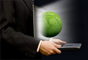 businessman with an open laptop and a green earth globe coming out of the screen